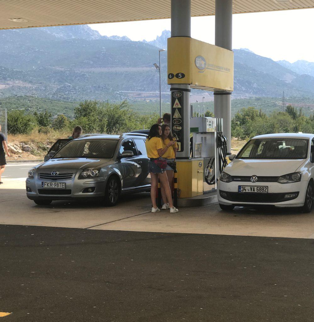 Hırvatistan tatili sırasında benzin istasyonunda araçların camlarını silmek için bekleyen genç kızlar